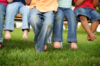 Photo showing legs and feet of children sitting on a bench