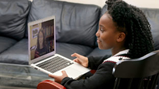 A young girl holding a computer demonstrates how a child could use a computer to interact with a doctor.