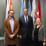 Nick Bratvold with Senator Thune and NCA's Denise Edwards in the senator's office, standing in front of flags.
