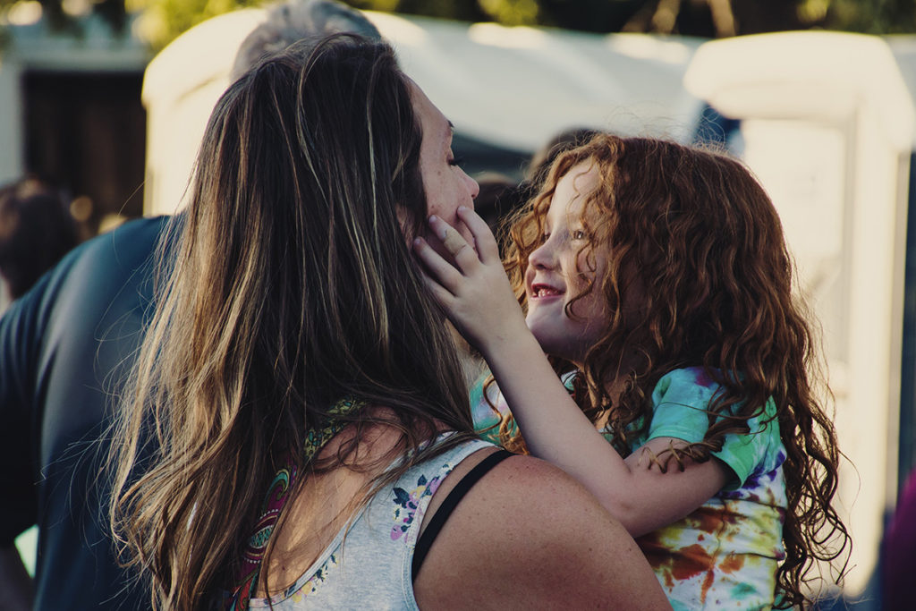 Photo of a smiling girl in her mom's arms